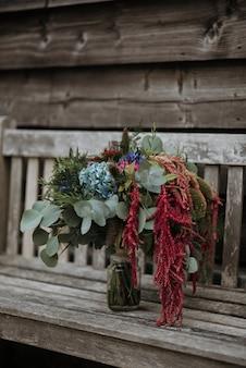 Colpo verticale di un mazzo di fiori in un vaso di vetro su una panca di legno