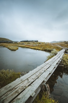 Vertical shot fo a wooden dock over a lake in finse, norway