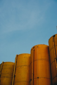 Vertical shot of four yellow metallic silos with the blue sky