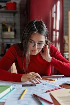 Colpo verticale della giovane donna castana lentigginosa si siede a casa con la carta di credito