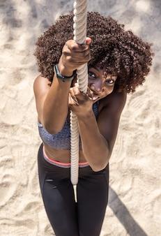 검은색과 회색 운동복을 입고 서서 모래 바닥을 배경으로 밧줄을 오르는 젊은 흑인 여성 아프리카 머리의 위에서 수직 샷
