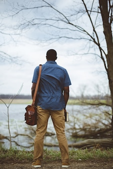 Вертикальный снимок сзади мужчины, который носит сумку и держит библию