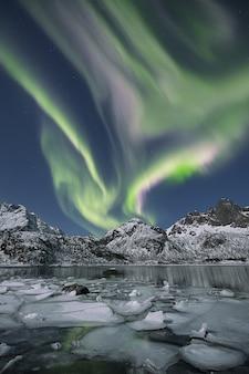 Colpo verticale di un lago ghiacciato circondato da colline innevate sotto l'aurora boreale