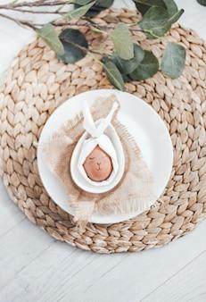 Colpo verticale di un divertente arredamento uovo di pasqua in un piatto con foglie verdi