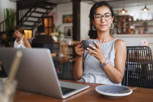 Colpo verticale dolce tenera donna urbana rilassata con gli occhiali godendo il momento seduto da solo nella caffetteria