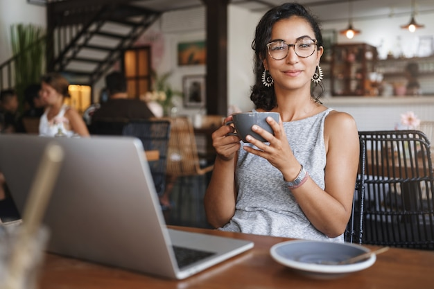 Вертикальный снимок нежной нежной расслабленной городской женщины в очках, наслаждающейся моментом, сидя в одиночестве в кафе
