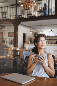 세로 샷 카페에 혼자 앉아 순간을 즐기는 안경을 쓰고 부드러운 부드러운 편안한 도시 여자