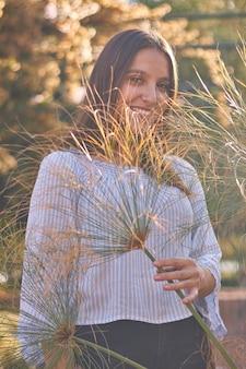 Colpo verticale di una ragazza che guarda la telecamera attraverso foglie sottili della pianta