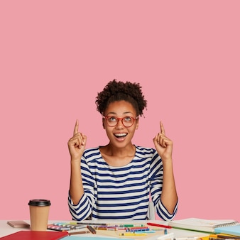 Vertical shot of glad dark skinned lovely woman artist, points with both index fingers, wears striped sweater, models against pink wall, feels excited, poses at desktop with spiral notebook