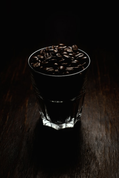 Vertical shot of a glass cup filled with coffee beans on a wooden surface with a black background