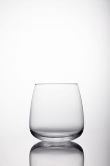Vertical shot of glass for water on a reflecting surface