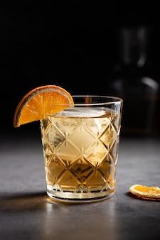 Colpo verticale di un bicchiere di whisky decorato con una fetta di arancia essiccata