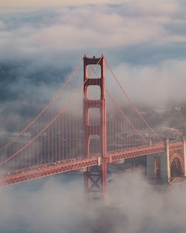 Vertical shot of the golden gate bridge covered in the fog