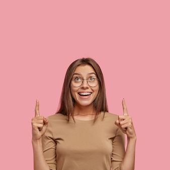 Colpo verticale di bella donna bruna con un ampio sorriso, guarda con gioia al rialzo, indica con le dita indice