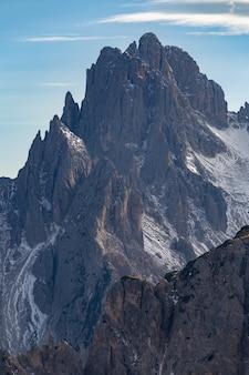 Colpo verticale di una splendida vetta di una roccia nelle alpi italiane sotto il cielo nuvoloso al tramonto