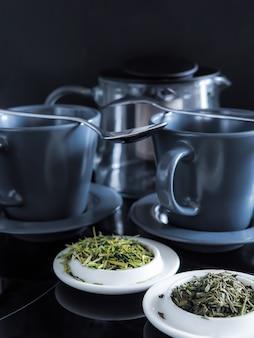 Colpo verticale di tè verde, tazze da tè e una casa da tè