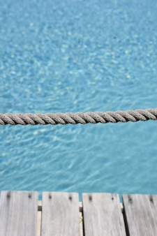 Vertical shot of a grey rope with the background of the clear water in the pool
