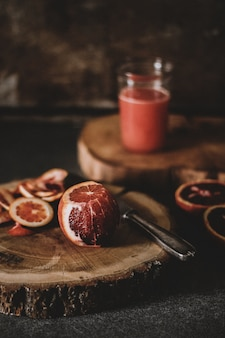 Vertical shot of a half peeled blood orange near a knife on a round wooden slab
