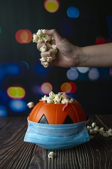 Vertical shot of a halloween pumpkin with popcorn and a sanitary mask