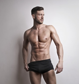 Vertical shot of handsome athletic male with naked torso