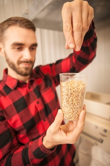 Vertical shot of a handsome bearded brewer examining barley seeds, working at his beer factory