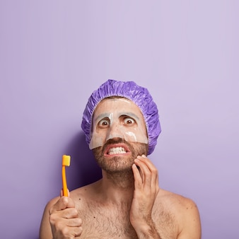 Vertical shot of handsome male model touches thick bristle, wears moisturising mask for skin softness, clenches teeth, holds toothbrush