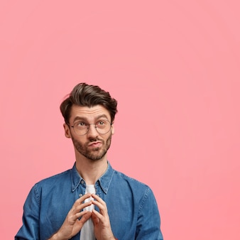 Vertical shot of handsome pensive unshaven young male, keeps hands pressed together, looks pensively upwards, dressed in elegant denim shirt, isolated over pink wall with copy space aside