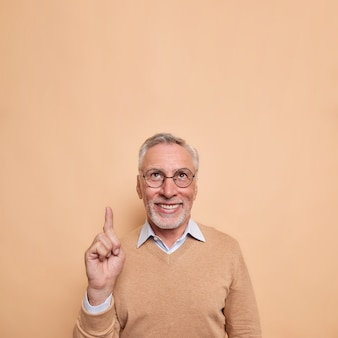 Vertical shot of happy bearded mature man points index finger above shows blank space