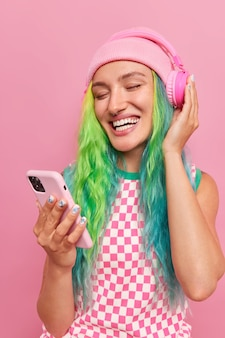 Vertical shot of happy carefree teenager with long colorful hair chooses favorite song from playlist holds mobile phone wears wireless headphones wears hat and dress isolated on pink