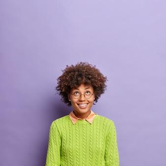 Colpo verticale di sorrisi felici della giovane donna dai capelli ricci ampiamente concentrati sopra