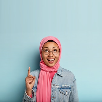 Vertical shot of happy dark skinned female muslim woman poses over blue space
