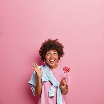 Vertical shot of happy dark skinned girl looks above with glad face expression, smiles broadly and raises hand, holds delicious lollipop, sees something amazing upwards, isolated on pink wall