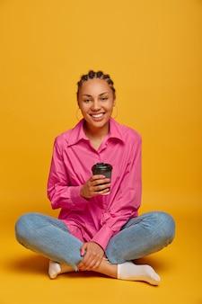 Vertical shot of happy dark skinned woman sits in lotus pose, crossed legs on floor, drinks takeaway coffee, feels comfortable, enjoys friendly conversation with interlocutor, isolated on yellow wall