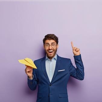 Colpo verticale di felice regista maschio in elegante abbigliamento formale, punta il dito indice sopra