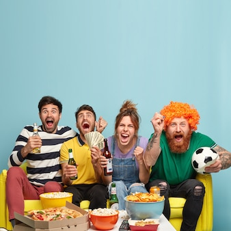 Vertical shot of happy three men and one woman, watch emotionally football match, support favourite team