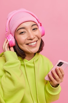 Vertical shot of happy young asian woman dressed in casual clothes enjoys favorite music wears headphones on ears with good sound quality holds modern smartphone isolated over pink wall.