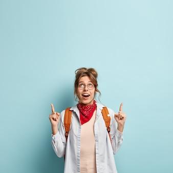 Il colpo verticale di felice giovane femmina indica sopra con entrambe le dita anteriori, mostra un prodotto fantastico in cima, indossa abiti casual alla moda