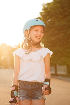 Vertical shot of a happy young girl laughing joyfully, wearing rollerblading helmet