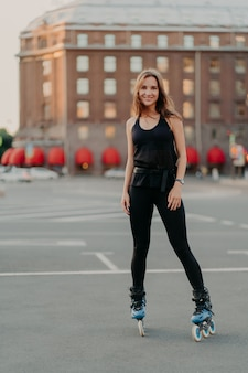 Vertical shot of healthy slim woman going rollerblading dressed in active wear spends free time outdoors smiles happily has exercising activities leads sporty lifestyle. inline skating concept