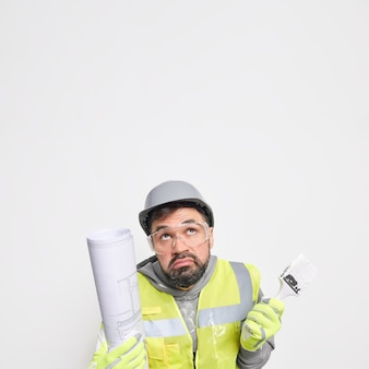Vertical shot of hesitant male construction worker makes renovation in new house holds blueprint and paint brush concentrated clueless above