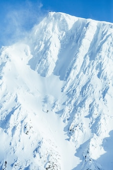 Vertical shot of a high mountain range covered with snow under the clear blue sky