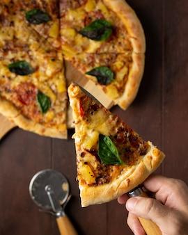 Ripresa verticale di una pizza fatta in casa su una superficie di legno