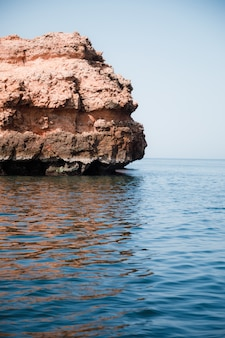 Vertical shot of a huge stone in the middle of the calm sea