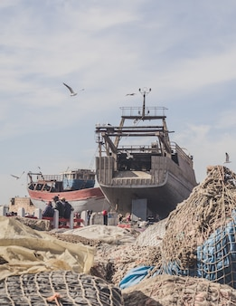 Vertical shot of an incomplete ship next to a lot of fishing nets with seagulls flying above