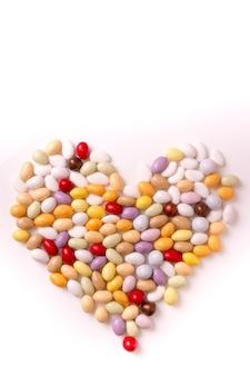 Colpo verticale di jellybeans a forma di cuore e isolato su uno sfondo bianco