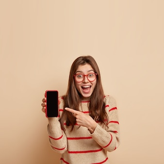 Vertical shot of joyful caucasian female points at smart phone device, shows black blank screen for your advertising text, laughs, has pleased expression, isolated over beige wall with free space