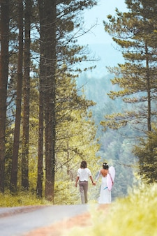 Vertical shot of  a just married couple in a forest with a surfboard holding their hands