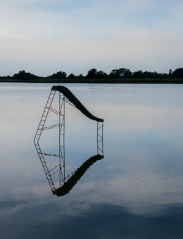 Vertical shot of a lake with a water swing reflected in the water and trees on the background