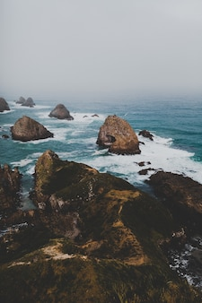 Vertical shot of large rocks in nugget point ahuriri, new zealand