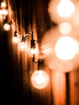 Vertical shot of lit lightbulbs on an electrical wire near a wooden fence